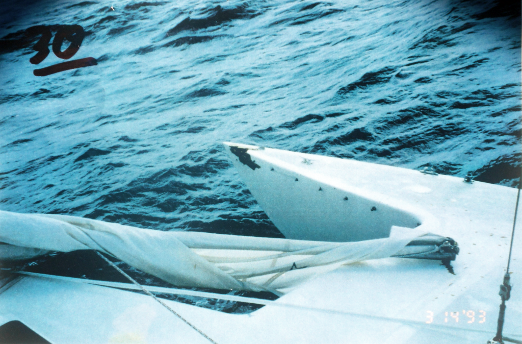"Gold Eagle of Raleigh, showing damaged starboard ama after the trimaran survived a freak storm in the Gulf of Mexico. ""I am not sure exactly when, but I suspect probably when the rogue wave hit, the sea anchor also tore loose a bridle leg, carrying with it the hardware for mounting the trampoline, because, sometime after daybreak we noted that the bridle for the right side of the sea anchor was totally gone. There was a hole in the bow on the right side [starboard ama], and the boat was riding to the sea anchor from one line, which was cleated off to the left side of the main bow."" (Andrew Cserny photo)."
