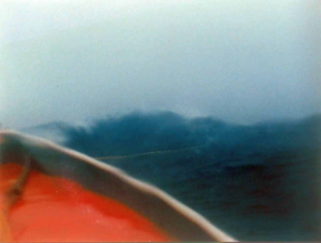 "Holly tethered to a 28-ft. diameter C-9 parachute in 18-ft. seas during a November gale about 75 miles SE of Nantucket. Note the breaking crest to the left, and the rode leading to the sea anchor. ""Through the toughest twenty hours of the storm we lay to the parachute.... The PARA-28 kept our bow into the seas as we drifted. We did not pound into the seas, nor did we lie beam-to. It was a soft, comfortable manner to ride out the storm."" (Photo courtesy of Captain Marc Palombo, Calico Lobster, Inc.)"